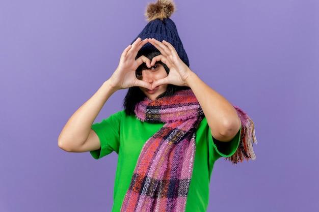 Jonge zieke vrouw die de wintermuts en sjaal draagt die hartteken doen die voorzijde door het geïsoleerde op purpere muur met exemplaarruimte kijken