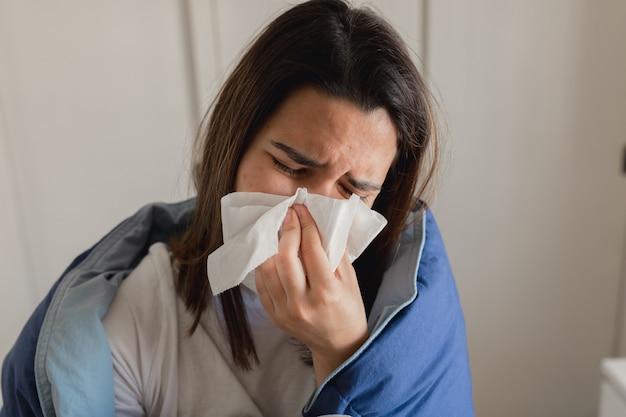 Jonge zieke vrouw die in een weefsel niest terwijl het behandelt met een blauw dekbed in haar huis