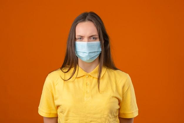 Jonge zieke vrouw die in geel poloshirt en medisch beschermend masker camera op oranje achtergrond bekijken