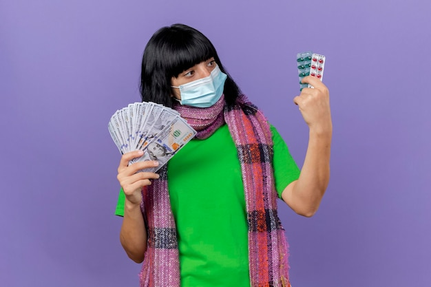 Jonge zieke vrouw die masker en sjaal draagt die geld en verpakkingen van capsules houdt die capsules bekijken die op purpere muur met exemplaarruimte worden geïsoleerd