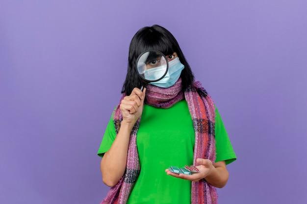 Jonge zieke vrouw die masker en sjaal draagt die pakken van capsules houdt die voorzijde door vergrootglas bekijkt dat op purpere muur met exemplaarruimte wordt geïsoleerd