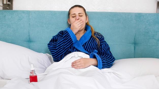Jonge zieke vrouw hoest en sluit haar mond met de hand
