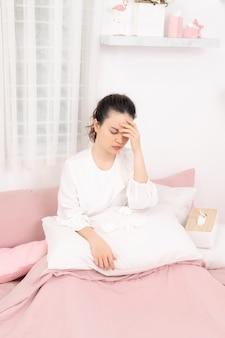 Jonge zieke vrouw in bed thuis