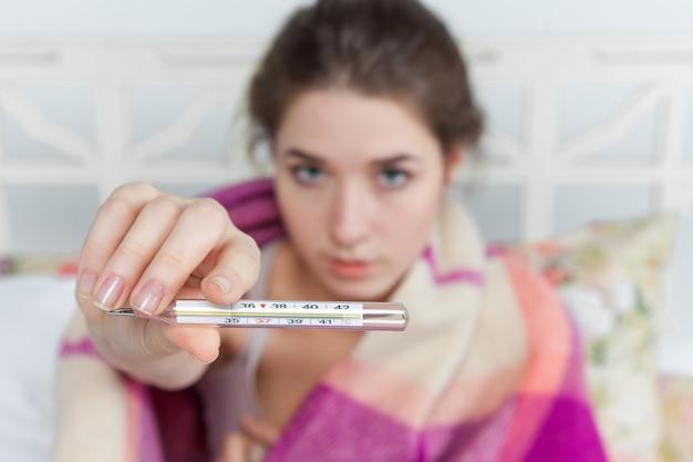 Jonge zieke vrouw in deken met thermometer