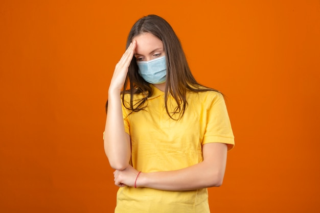 Jonge zieke vrouw in geel poloshirt en medisch beschermend masker wat betreft hoofd en het denken op geïsoleerde oranje achtergrond