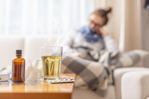 Jonge zieke vrouw liggend onder deken op een bed met seizoensgebonden ziektes die hete thee drinken met honing en citroen. ze neemt pillen en hoestsiroop om de ziekte te duwen.