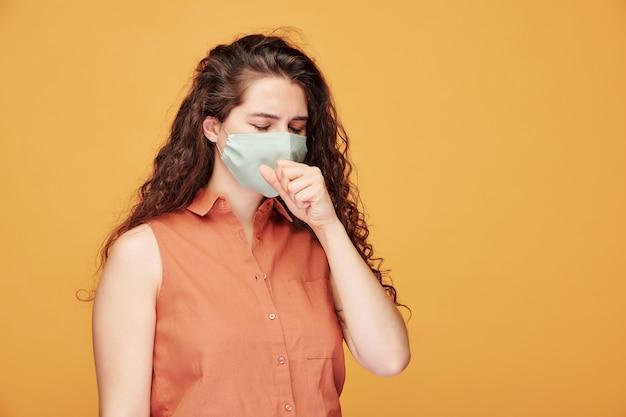 Jonge zieke vrouw met coronavirus hoesten door beschermend masker terwijl ze voor camera tegen gele muur staat