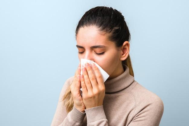 Jonge zieke vrouw met virus niezen en hoesten in een servet