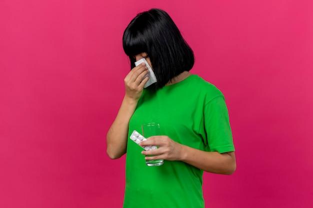 Jonge zieke vrouw staande in profiel te bekijken met medische tabletten en glas water afvegende neus met servet geïsoleerd op roze muur met kopie ruimte