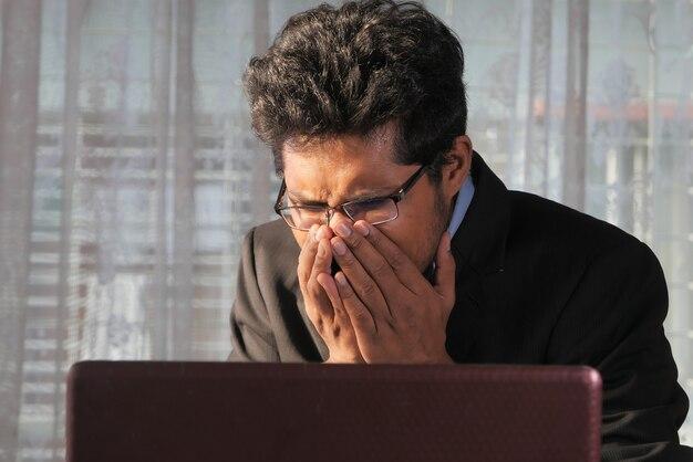 Jonge zieke zakenman hoesten tijdens het werken op laptop.