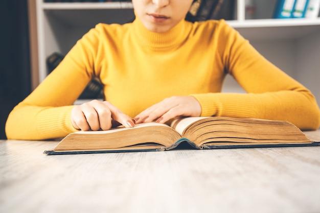 Jonge zittende vrouw leesboek