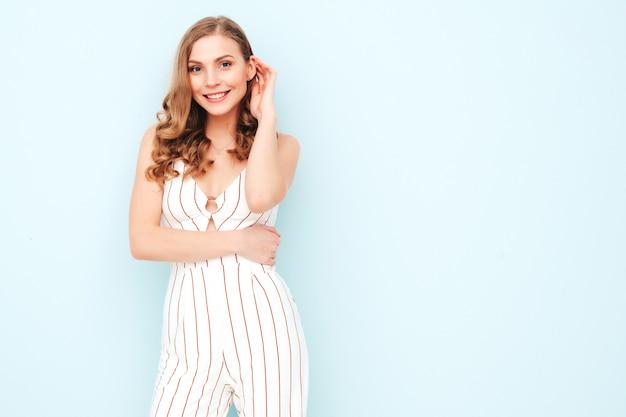 Jonge zorgeloze vrouw poseren in de buurt van lichtblauwe muur in studio