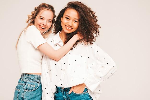 Jonge zorgeloze vrouwen poseren op grijze muur in studio