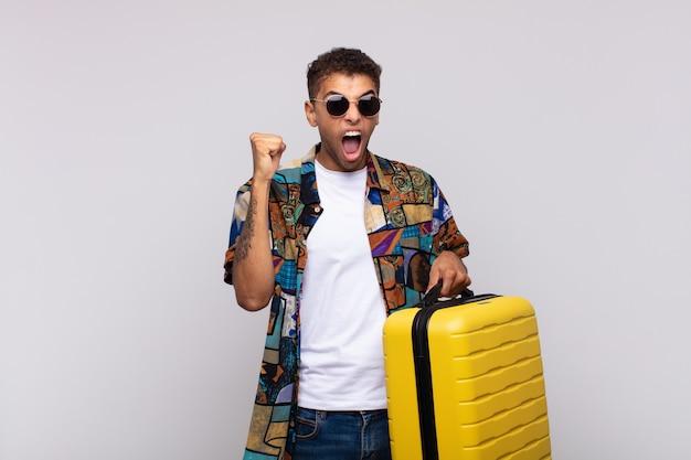 Jonge zuid-amerikaanse man die agressief schreeuwt met een boze uitdrukking of met gebalde vuisten om succes te vieren