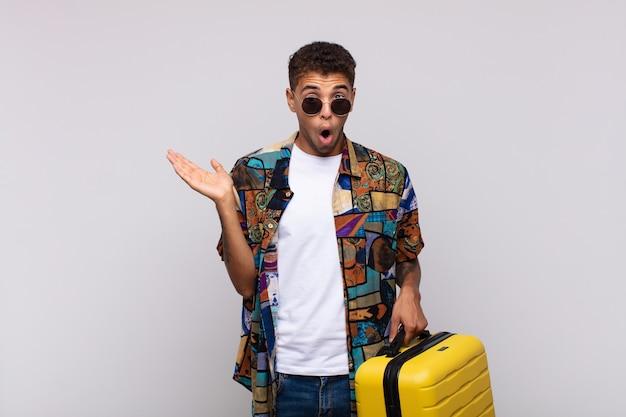 Jonge zuid-amerikaanse man die verbaasd en geschokt kijkt, met open mond een voorwerp vasthoudend met een open hand op de zijkant