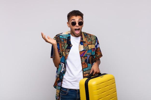 Jonge zuid-amerikaanse man die zich blij, opgewonden, verrast of geschokt voelt, glimlacht en verbaasd is over iets ongelooflijks