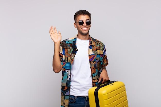 Jonge zuid-amerikaanse man lacht vrolijk en opgewekt, zwaait met de hand, verwelkomt en begroet je, of neemt afscheid