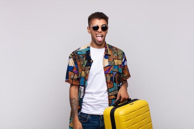 Jonge zuid-amerikaanse man met een vrolijke, zorgeloze, rebelse houding, grappen maken en tong uitsteken, plezier maken