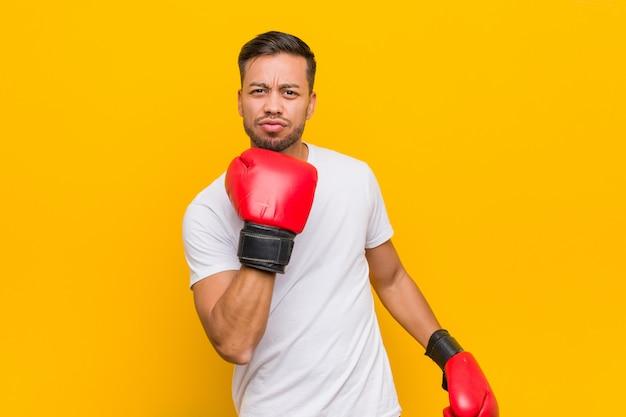 Jonge zuid-aziatische boksermens die rode handschoenen draagt.