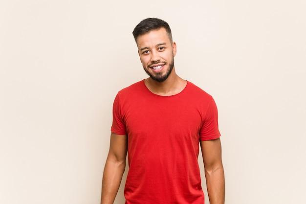 Jonge zuid-aziatische man blij, glimlachend en vrolijk.