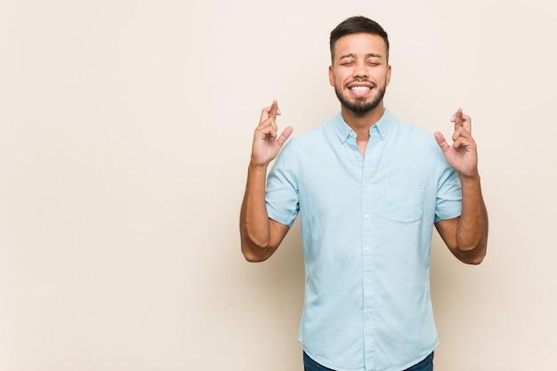 Jonge zuid-aziatische man die vingers kruist voor geluk