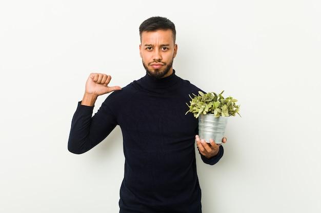 Jonge zuid-aziatische man met een plant voelt zich trots en zelfverzekerd