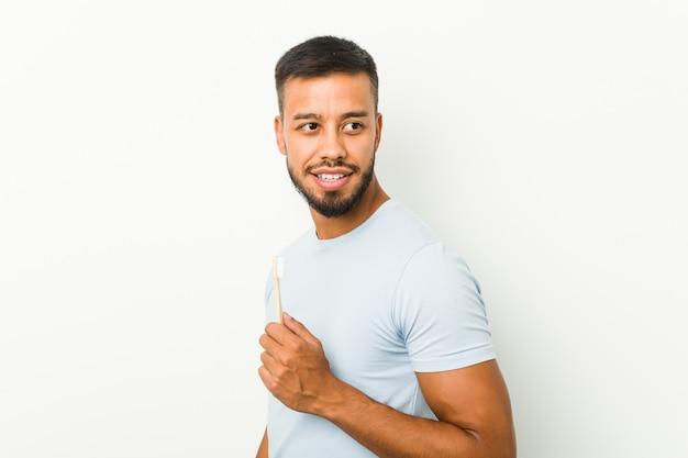 Jonge zuid-aziatische man met een tandenborstel kijkt opzij lachend, vrolijk en aangenaam.