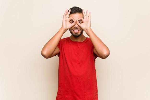 Jonge zuid-aziatische mens die ok teken over ogen toont