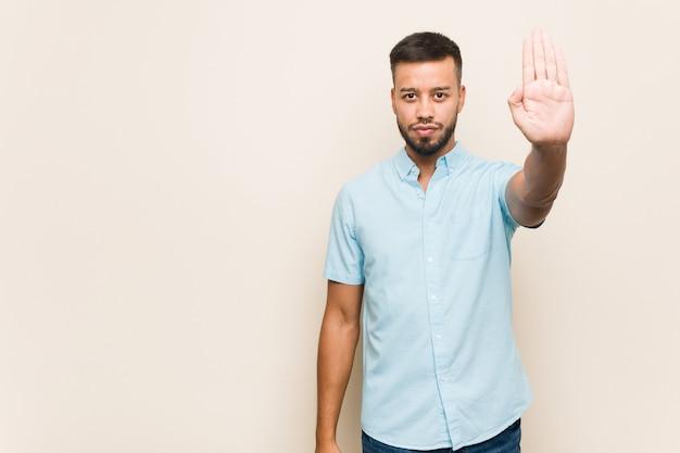 Jonge zuid-aziatische mens die zich met uitgestrekte hand bevindt die stopteken toont, dat u verhindert.