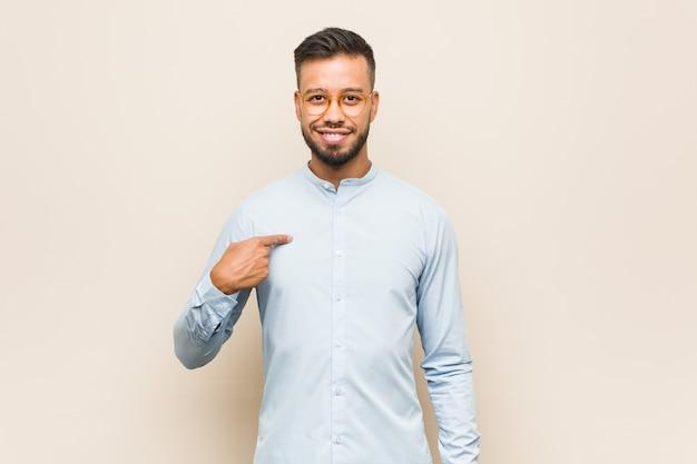 Jonge zuidaziatische bedrijfsmensenpersoon die met de hand naar de ruimte van een overhemdskopie wijst, trots en zelfverzekerd