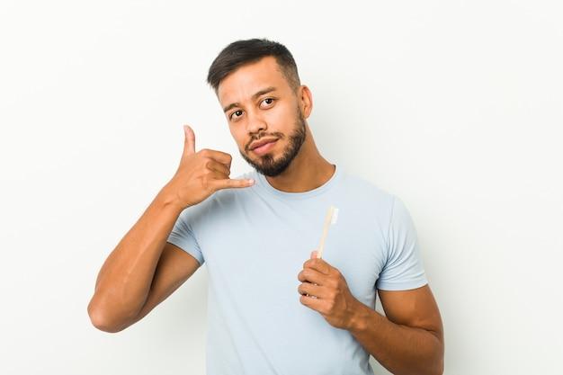 Jonge zuidaziatische mens die een tandenborstel houdt die een gsm-gebaar met vingers toont.