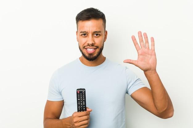 Jonge zuidaziatische mens die een vrolijke tv-controller houdt die nummer vijf met vingers glimlachen.