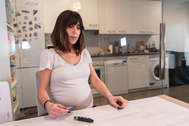 Jonge zwangere brunette die een zwangerschapsdiabeteszelftest uitvoert om suiker te controleren