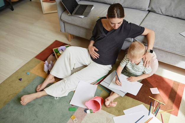 Jonge zwangere moeder zit op tapijt in de woonkamer en omhelst zoon terwijl ze thuis tijd met hem doorbrengt