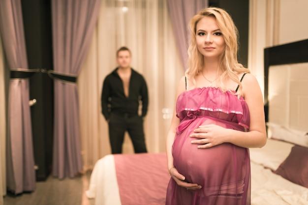 Jonge zwangere mooie vrouw houdt haar buik vast terwijl ze tegen een wazige vermoeide echtgenoot staat