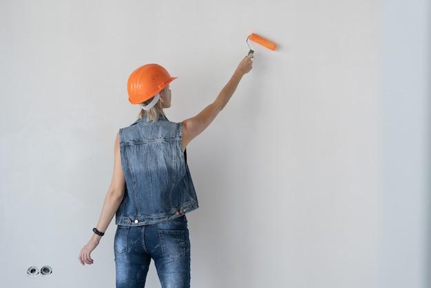 Jonge zwangere mooie vrouwenbouwer in een oranje beschermende helm op haar hoofd. zwanger meisje. verf de muur met een verfroller. plaats voor tekst