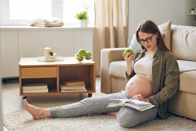 Jonge zwangere rustgevende vrouw in vrijetijdskleding boek lezen en groene appel eten zittend op de vloer door bank thuis