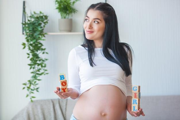 Jonge zwangere vrouw binnenshuis. close-upportret van vrouw het verwachten. mooi wijfje dat op haar kleine babygeboorte wacht.