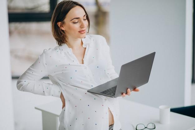 Jonge zwangere vrouw die aan computer buiten het bureau werkt