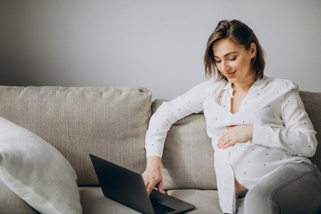 Jonge zwangere vrouw die aan laptop thuis werkt