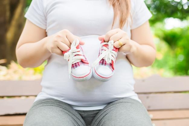 Jonge zwangere vrouw die baby schoenen aan haar buik