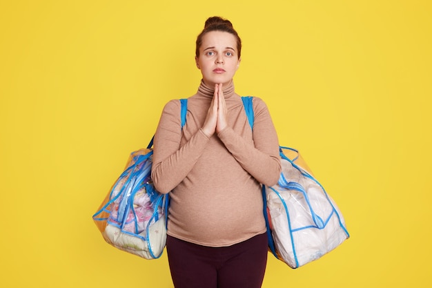 Jonge zwangere vrouw die bidt voor haar toekomstige baby, wenst dat alles goed komt, poseert met tassen vol spullen voor baby en aanstaande moeder, staande tegen gele muur.