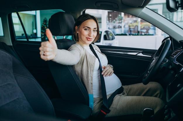 Jonge zwangere vrouw die een auto in autotoonzaal testen