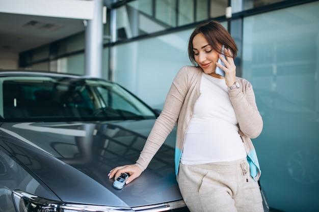 Jonge zwangere vrouw die een auto in een autotoonzaal kiest