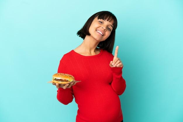 Jonge zwangere vrouw die een hamburger over een geïsoleerde achtergrond houdt die een vinger toont en opheft
