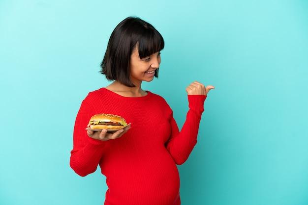 Jonge zwangere vrouw die een hamburger over een geïsoleerde achtergrond vasthoudt en naar de zijkant wijst om een product te presenteren
