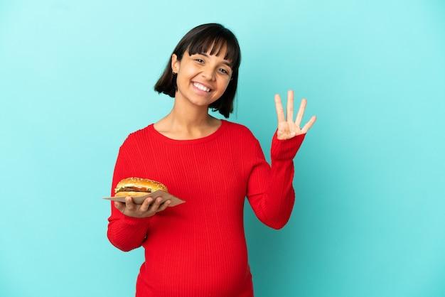 Jonge zwangere vrouw die een hamburger over geïsoleerde achtergrond gelukkig houdt en vier met vingers telt