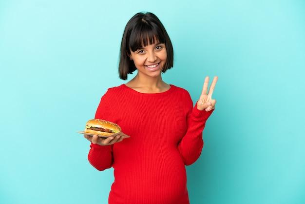 Jonge zwangere vrouw die een hamburger over geïsoleerde achtergrond houdt die glimlacht en overwinningsteken toont