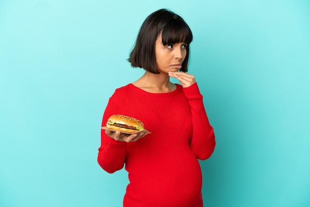 Jonge zwangere vrouw die een hamburger over geïsoleerde achtergrond houdt die twijfels heeft