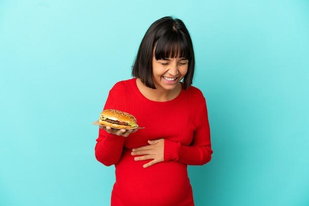 Jonge zwangere vrouw die een hamburger over geïsoleerde achtergrond houdt die veel glimlacht